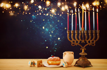 image of jewish holiday Hanukkah background with menorah (traditional candelabra) and candles over glitter shiny background.