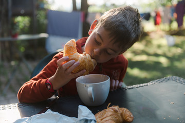 boy dunking his croissant in hot chocolate