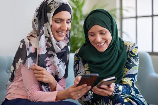 Muslim women comparing photos on smart phones modern lifestyle