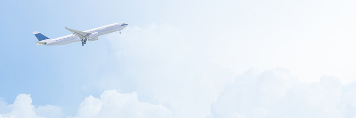Commercial airplane flying over bright blue sky and white clouds. Photo Design in banner cover size with copy space for travel concept.