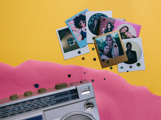 Polaroid prints spread out on top of yellow and pink ripped paper with a 1980s ghetto blaster and confetti