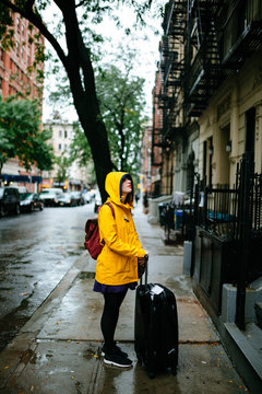 a woman in the streets of new york with a yellow raincoat and a suitcase