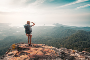 Young woman hiker stands with backpack on the cliff and looks into valley and sea coastline
