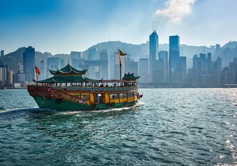 Fotobehang Hong-Kong Passenger boat carrying tourists between the Islands of Hong Kong with modern skyscrapers in the background