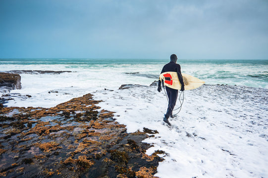 Surfer heading into the ocean