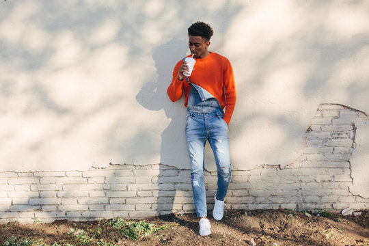 Portrait of a cool black man drinking a refreshment outdoors.