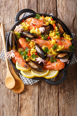 Closeup of traditional Spanish paella with seafood in a pan. Vertical top view from above