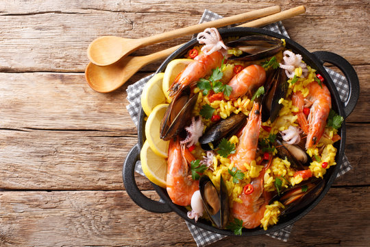 Spanish traditional cuisine: hot paella with seafood shrimps, mussels, fish, and baby octopuses close-up in a frying pan. horizontal top view