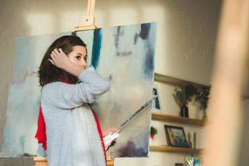 Portrait of beautiful female artist standing against paintings in studio
