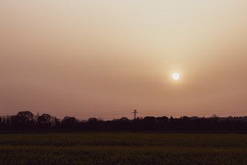 Sunset with sand suspended in the atmosphere, coluring the sky red, over some fields and hills