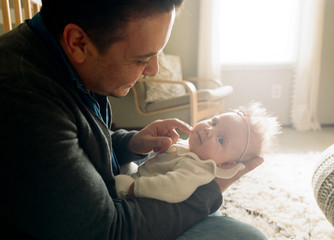 father holds baby girl in sunny nursery