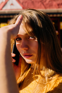 Cute young woman talking on phone and looking at camera