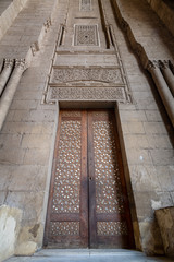 External old decorated bricks stone wall with arabesque decorated wooden door framed by stone ornate cylindrical columns leading to al Rifai Mosque, Old Cairo, Egypt
