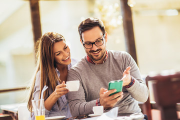 Young cheerful man and woman dating and spending time together in cafe, using phone.