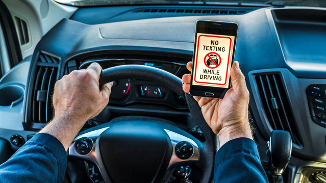 Close up of the hands of a man driver, holding phone in hand while driving, phone displays no texting while driving on screen. Very unsafe driving habit.