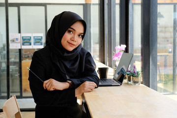 Working woman concept, Islam woman working in cafe with portrait shot on table.