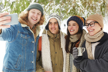 Waist up portrait of  happy young people taking selfie in beautiful snowy forest on winter resort