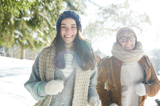 Portrait of two young women running towards camera while enjoying walk in beautiful winter forest in sunlight