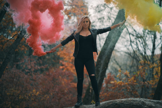 Girl with red and yellow smoke bombs