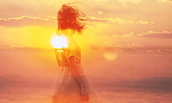 Double exposure of young woman and sunset sky.