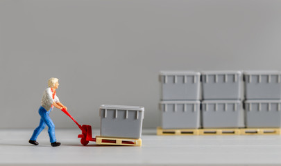 miniature warehouse man worker figure using a trolley towing hand to moving boxes