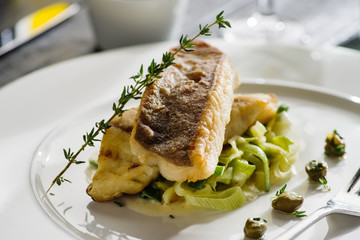 Fillet of halibut on a pillow of stewed leeks on the white plate.