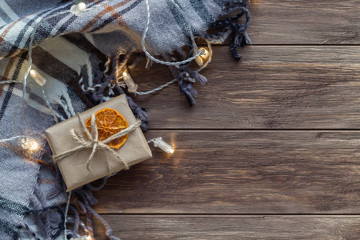 Christmas composition with plaid, lights and gift in craft paper on the wooden background. Flat lay, top view, copy space