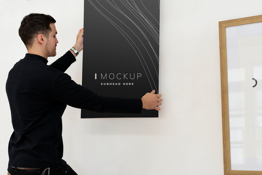 Curator hanging an art piece mockup on the wall in a gallery
