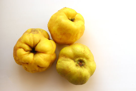 Ripe juicy yellow quince on a white background