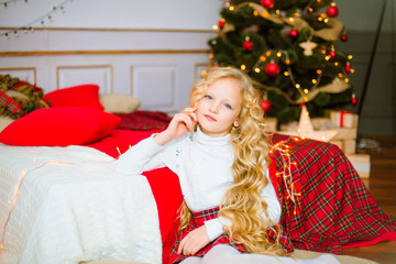 Little girl with blond long curly hair at Christmas morning.Merry Christmas.Little girl rejoices to the Christmas gift