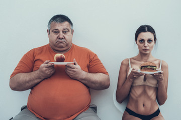Fat Man and Anorexic Girl with Plates with Food.
