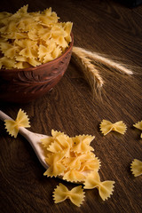 Pasta in the form of a butterfly in a wooden bowl on a wooden background near the ears of wheat. wooden spoon with pasta in the form of a butterfly