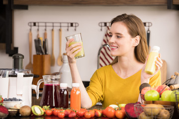 Healthy young woman in a kitchen with fruits and vegetables and juice