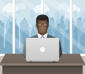 Black businessman working on laptop in an office on a cityscape background
