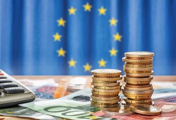 Geldscheine und Münzen vor der Flagge der Europäischen Union