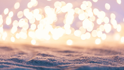 Winter background with snow and fairy lights.