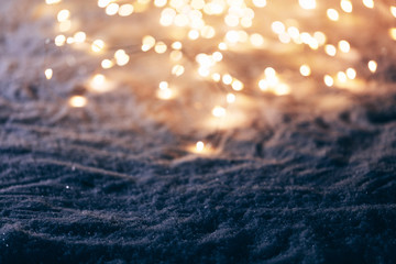 Snowy winter background with fairy lights.