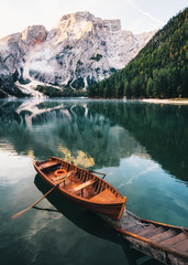 Door stickers Lake Boats and slip construction in Braies lake with crystal water in background of Seekofel mountain in Dolomites in morning, Italy Pragser Wildsee