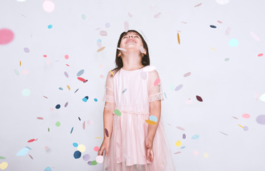 Beautiful little girl wearing pink dress in tulle with princess crown looking up to the colorful confetti surprise posing on white studio wall. Happy girl celebrating her birthday party, having fun