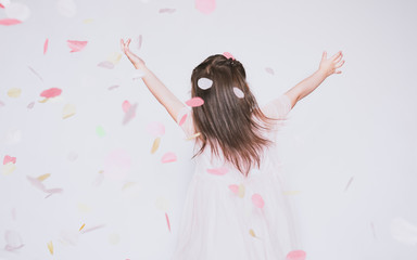 Rear view image of little girl wearing pink dress in tulle with princess crown on head isolated on white background rise hands up enjoy confetti. Cute girl celebrating her birthday party, having fun
