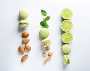 Composition with tasty macaroons, nuts, lime and mint on white background