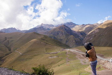 Young curly traveler taking photo with camera in Kazbegi.
