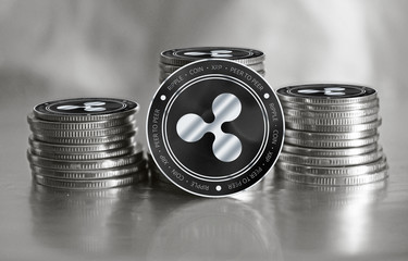 Ripple (XRP) digital crypto currency. Stack of black and silver coins. Cyber money.