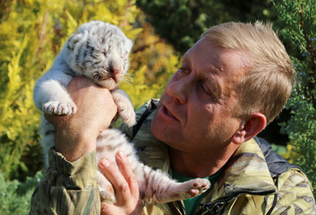 Taigan Safari Park director Oleg Zubkov holds a one-week-old White Bengal tiger cub at the park near Belogorsk