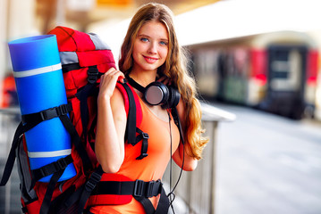 Traveller girl female wear headphones with backpack and tourism outfit at railway station city outdoor. Train locomotive on background.