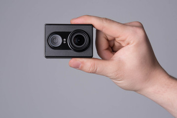 hand holding black action camera on grey background