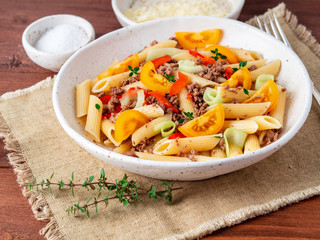 Penne pasta with yellow tomatoes, red and green vegetables, mincemeat on dark wooden background, side view
