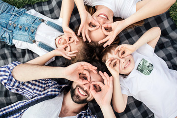 Funny picture of family doing funny rounds with their fingers on eyes. They are playing. All of them are lying on blanket and smiling. They look happy.