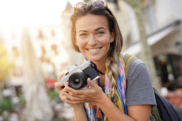 Attractive young woman taking photographs on SLR