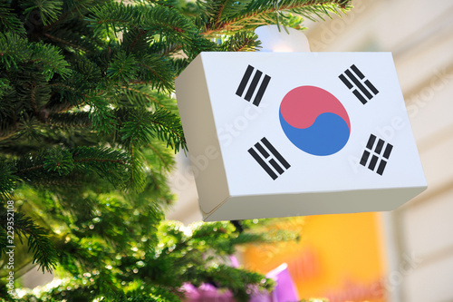 South Korea flag printed on a Christmas gift box. Printed present box decorations on a Xmas tree branch. Christmas shopping in South Korea, sale and deals ...